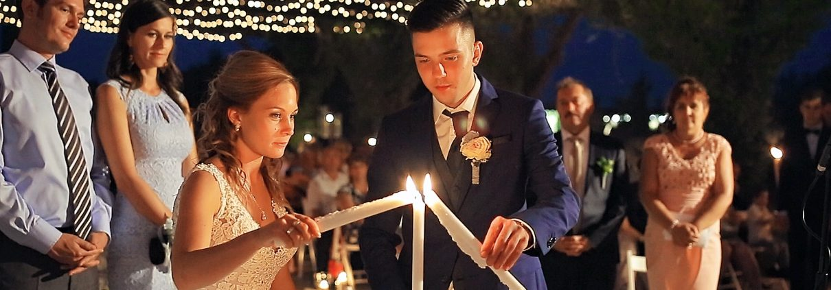 Bride and groom during ceremony - Couple holding candles at a wedding in Hungary